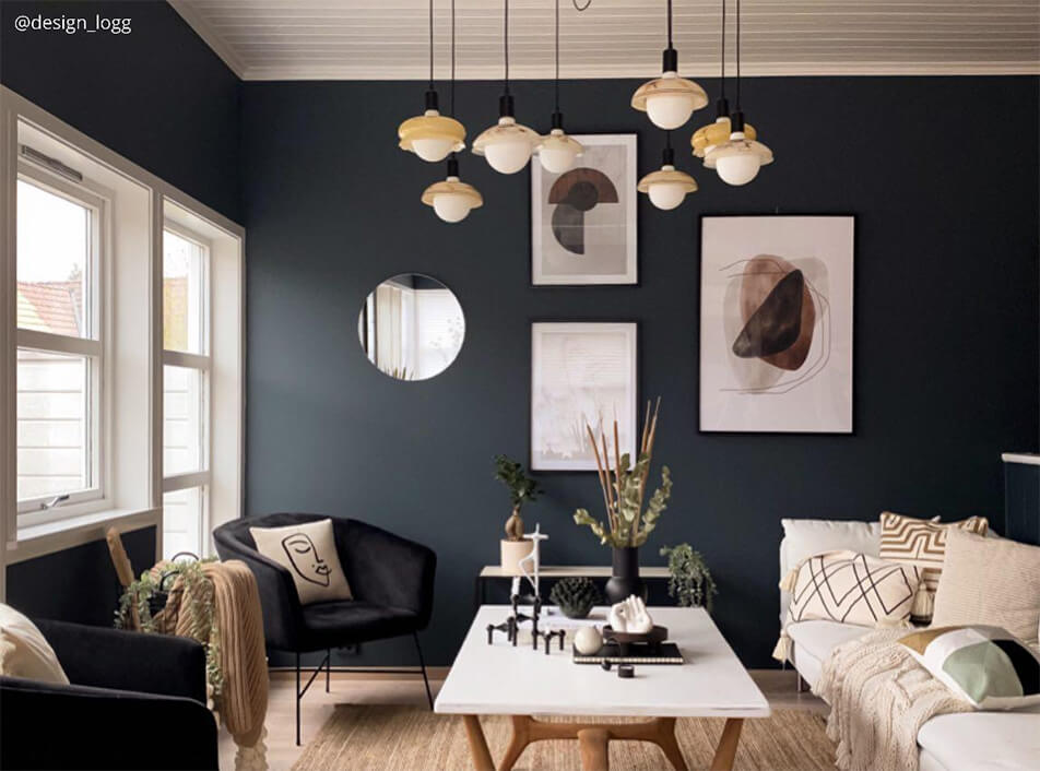 Sitting room with dark walls, black velvet armchairs, round mirror, graphical posters