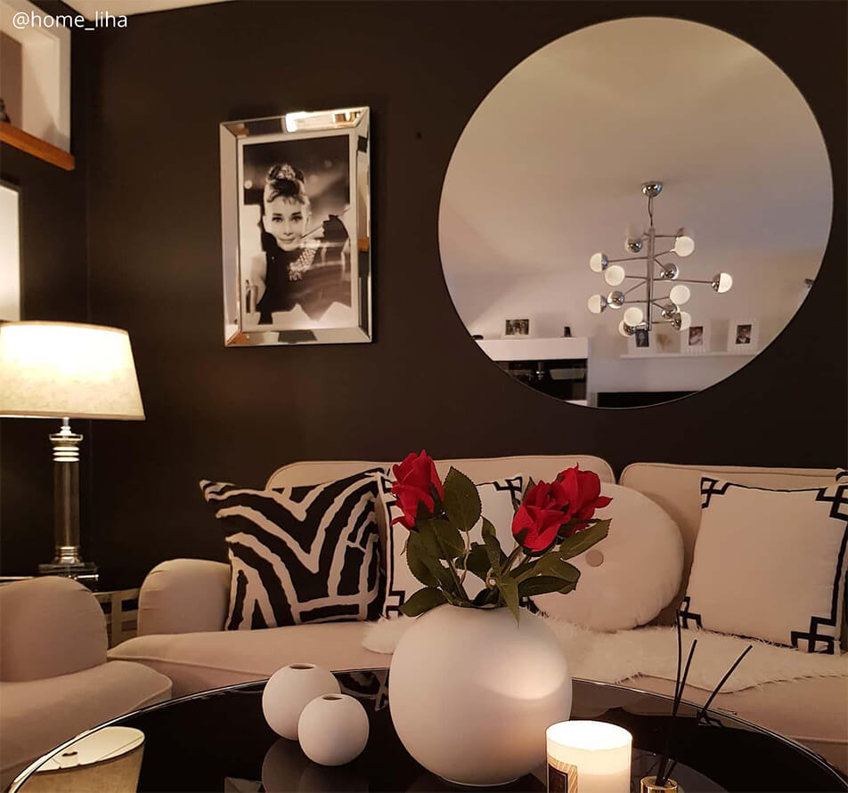 Sitting room with dark wall colour, white sofa and big, round mirror
