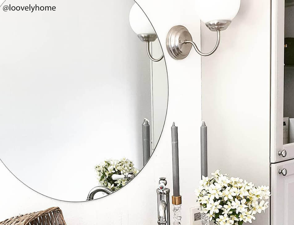 Round mirror, flowers and lights in bathroom